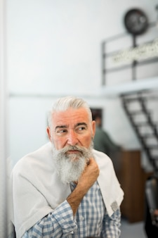 Old client checking beard after shaving at barbershop