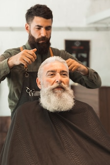 Old client getting haircut at hair salon