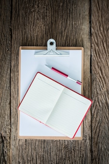 Old clipboard, red notebook, red pen on grungy wooden surface