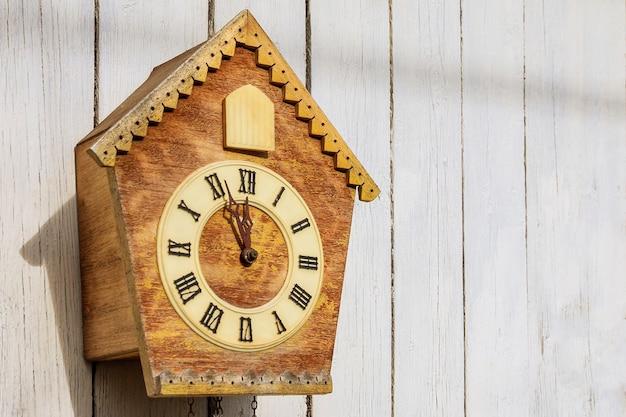 木製の光の壁に古い時計。ヴィンテージ時計。鳩時計。コピースペース。