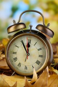 Старые часы на осенних листьях на деревянном столе на расфокусированной природе