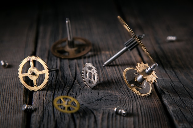 Old clockwork, gears, screws on wooden planks. good idea vintage, time from the inside. close-up, macro.