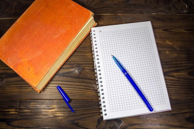 古い閉じた本、メモ帳、木製の机の上のペン