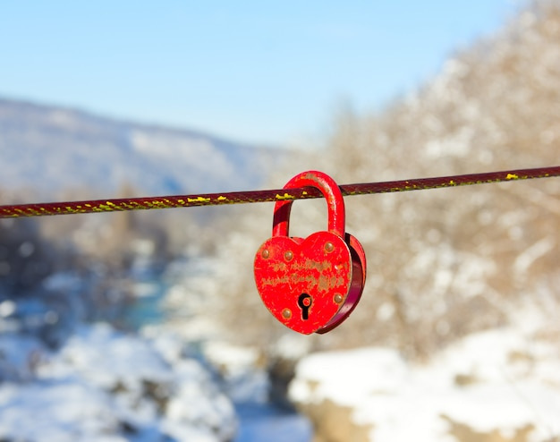 Old closed red padlock in heart shape on winter mountain landscape close up