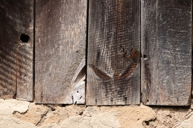 Old cob wall with cracked surface and old wooden boards