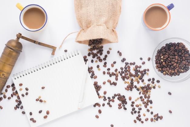 Старая кофемолка; кофейные зерна; чашка кофе; пустой спиральный блокнот с ручкой на белом фоне