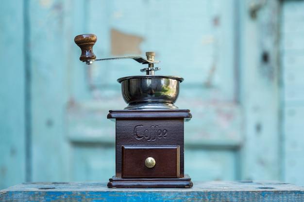 水色の木製の背景に古いコーヒーグラインダー。正面図。