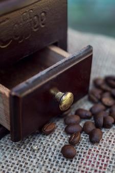 散在するコーヒー豆と水色の木製の背景に古いコーヒーグラインダー。垂直。閉じる。