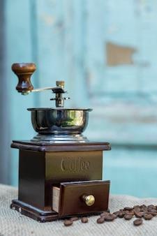 散在するコーヒー豆と水色の木製の背景に古いコーヒーグラインダー。垂直。