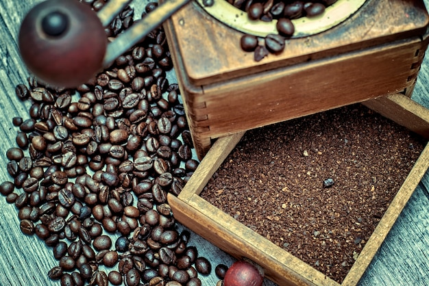 Old coffee grinder with ground coffee, coffee beans on a wooden background.