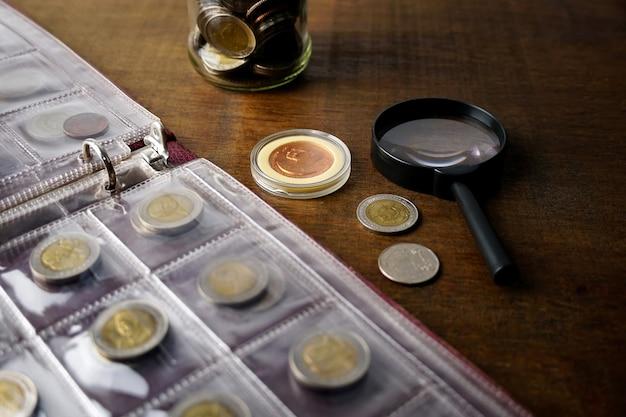 木製のテーブルの上の古い収集可能なコイン暗い背景バナー貨幣アルバムのコイン