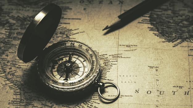 Old compass on antique map. - vintage background style.