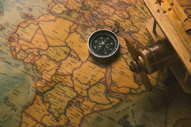 Открытие старого компаса и деревянный самолет на старинной бумажной антикварной карте мира