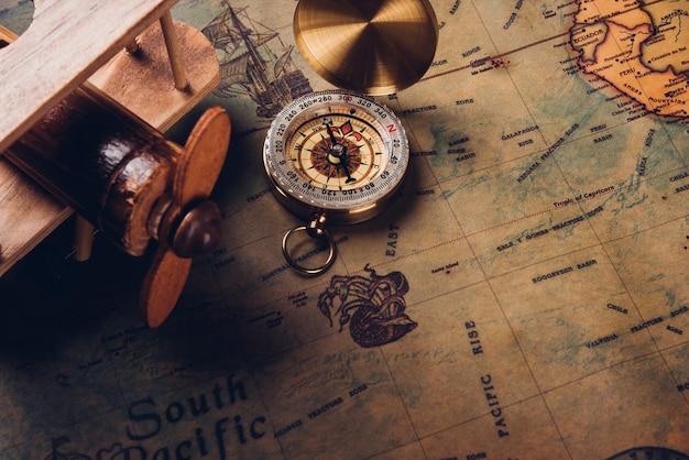 古いコンパスの発見とヴィンテージ紙のアンティークの世界地図上の木製の飛行機