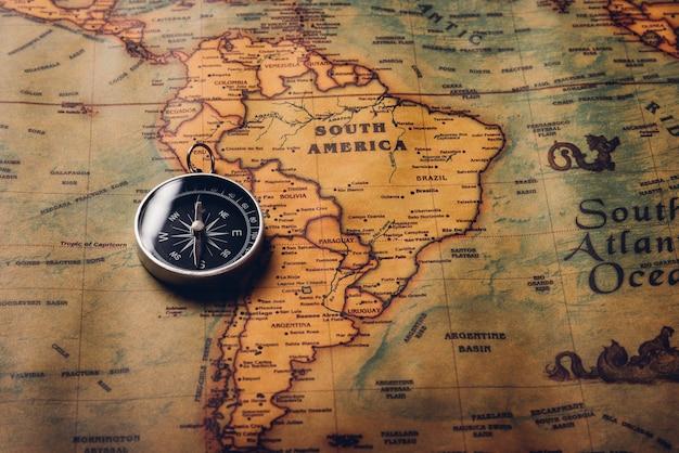 Открытие старого компаса на старинной бумажной антикварной карте мира