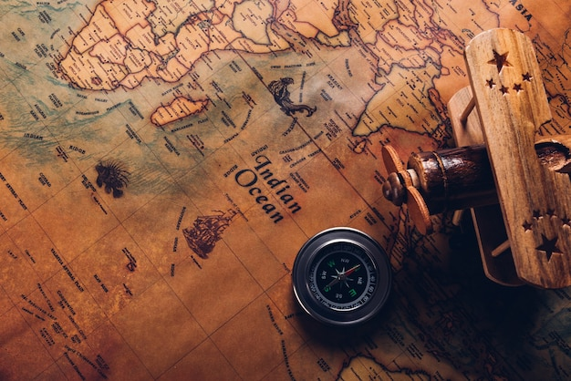 Old compass discovery and wooden plane on vintage paper antique world map background