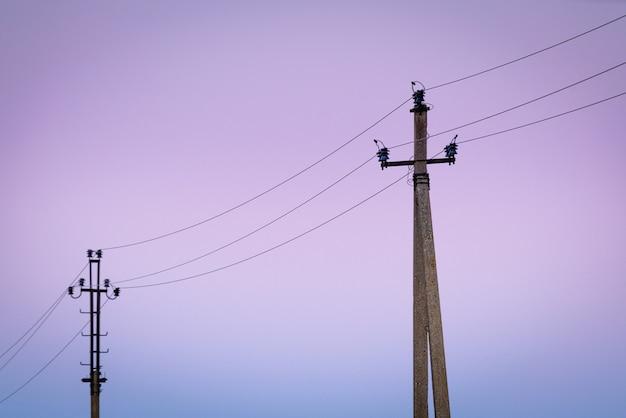 Старые бетонные столбы электричества в сумерках.