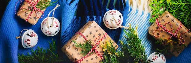상단에 따뜻한 격자 무늬가 있는 오래된 콘크리트 녹색 배경, 선물 상자 및 종소리. 소박한 빈티지 스타일입니다. 새 해의 배경입니다. 복사 공간이 있는 상위 뷰입니다.