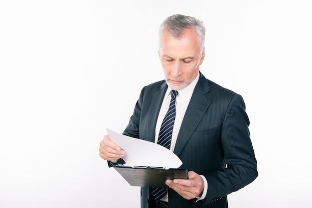 Старый уверенно бизнесмен, читающий информацию в папке
