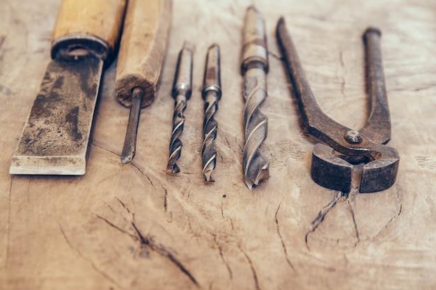 나무 작업대에 있는 오래된 건설 도구는 평평한 배경에 놓여 있습니다. 목수 테이블. 목조 부분.