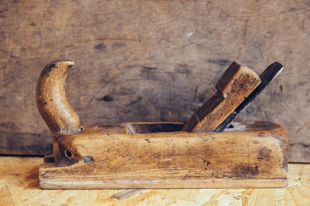 나무 작업대에 있는 오래된 건설 도구는 복사 공간이 있는 평평한 배경에 놓여 있습니다. 오래 된 목공 손 도구입니다.