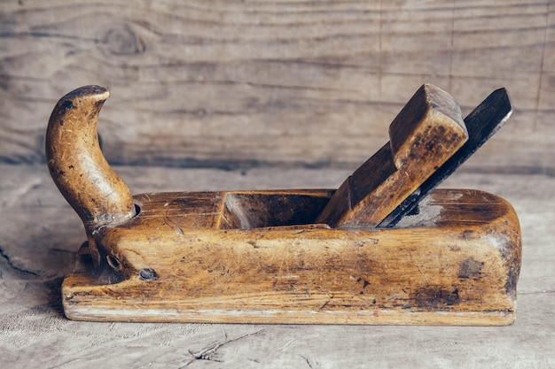 나무 작업대에 있는 오래된 건설 도구는 복사 공간이 있는 평평한 배경에 놓여 있습니다. 오래 된 목공 손 도구입니다. 프리미엄 사진