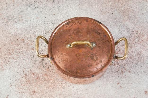 Старая медная кастрюля с крышкой и латунными ручками на бетонном столе.