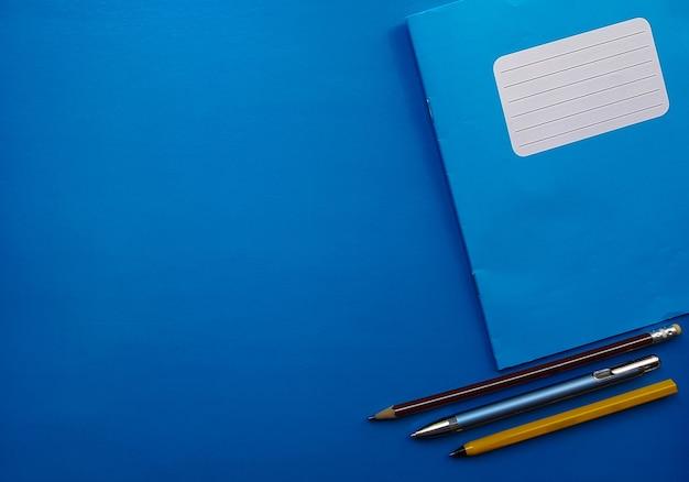 青い背景の古いコピーブック。学校のノート、9月1日と新学期の準備。