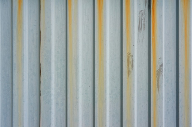 Old corrugated metal wall with rusty streaks.