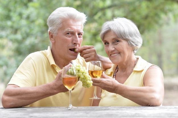 夏の庭でワインを飲み、ブドウを食べる老夫婦