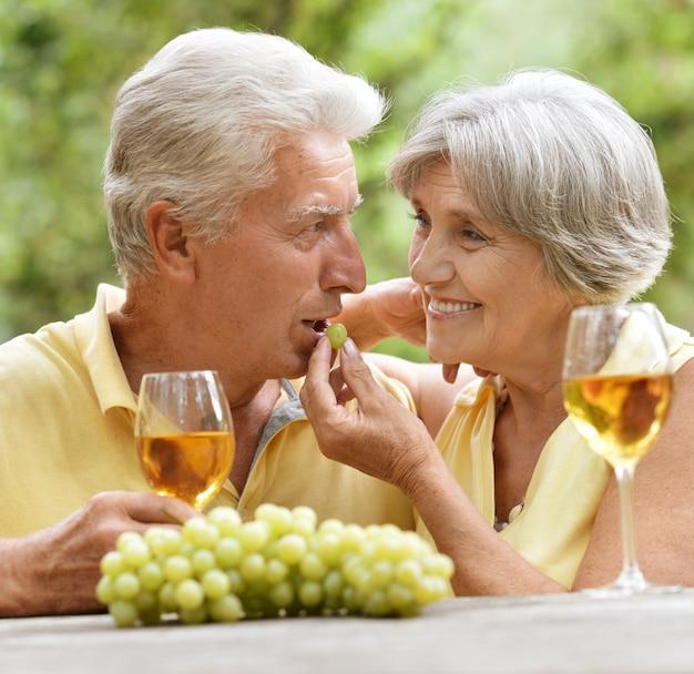 여름에 테이블에서 와인을 마시는 노부부