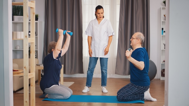Old couple exercise with nurse during their body rehabilitation. home assistance, physiotherapy, healthy lifestyle for old person, training and healthy lifestyle