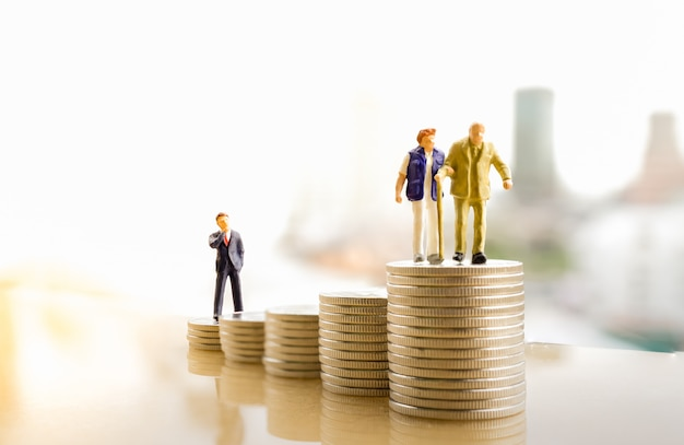 Old couple figure standing on top of coin stack with city backgrounds.
