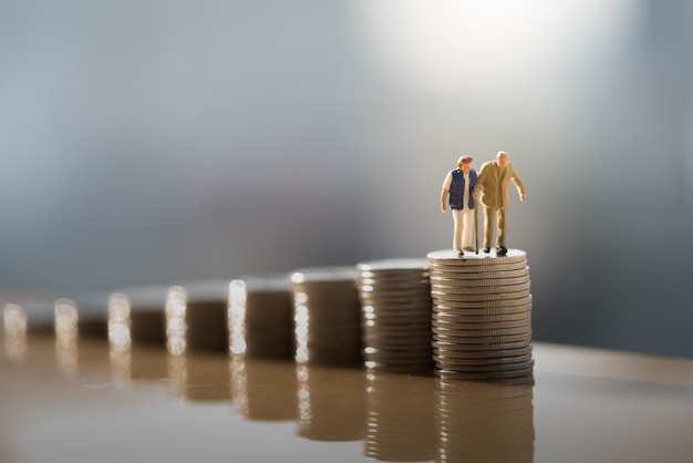 Old couple figure standing on top of coin stack with gray backgrounds.