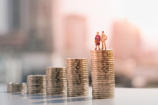 Old couple figure standing on top of coin stack.