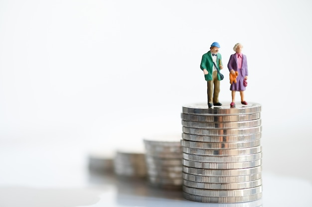 Old couple figure standing on top of stack coins using as background retirement planning .