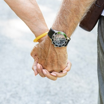 Old couple holding hands closeup