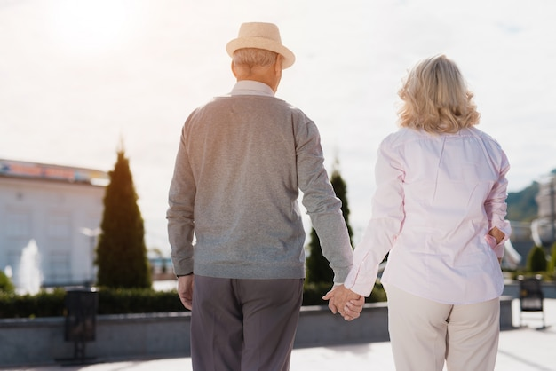 Old couple holding hands. elderly man in hat.