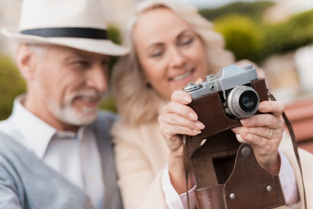 Old couple hugs. woman hold vintage camera.