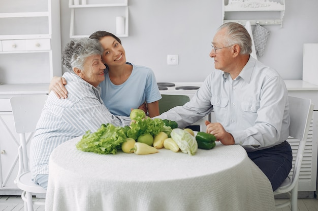 Old couple in a kitchen with young granddaughter