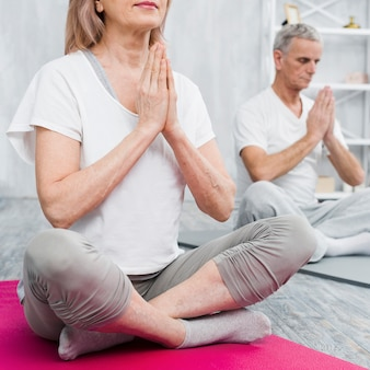 Old couple meditating at home with praying hands