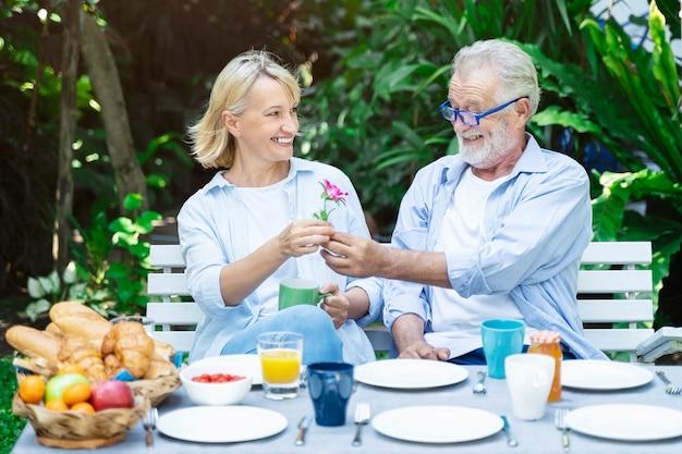 Старая пара людей встречаются со счастьем вместе в саду,