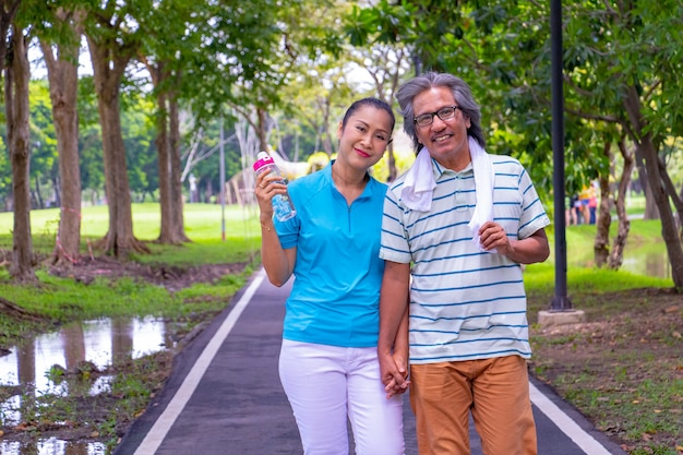 The old couple relax after jogging. they hold their hands and smile.