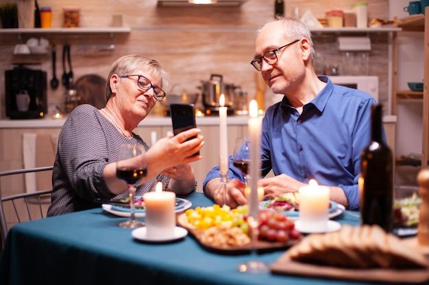 ロマンチックなディナーの間にキッチンで電話を使用している老夫婦。食堂のテーブルに座って、ブラウジング、検索、電話、インターネットの使用、食堂での記念日を祝う。
