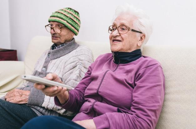 Старая пара смотрит телевизор