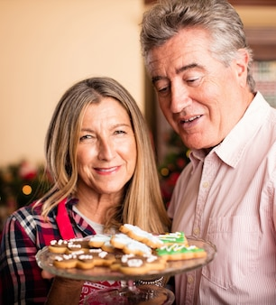 Old couple with a tray of christmas cookies