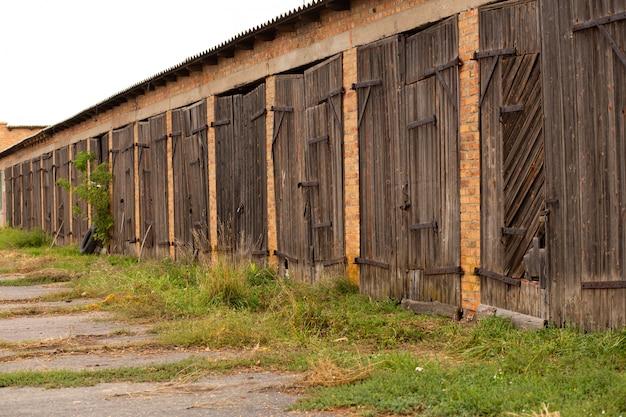 Старый коровник. большие деревянные ворота и сушеная древесина. старое кирпичное здание.
