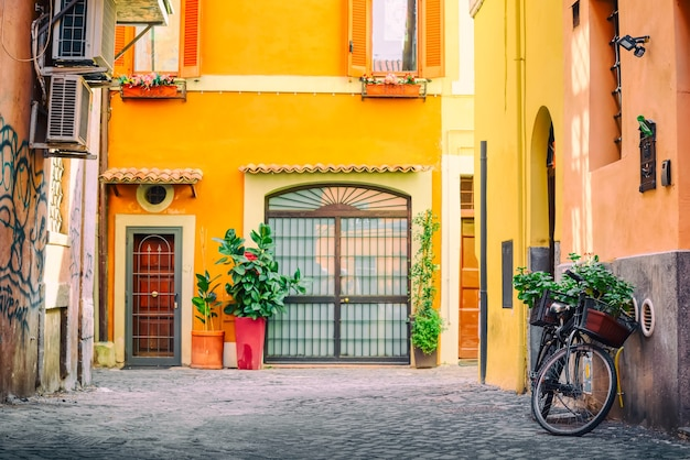 Old cozy street in trastevere, rome, italy with a bicycle and yellow house.