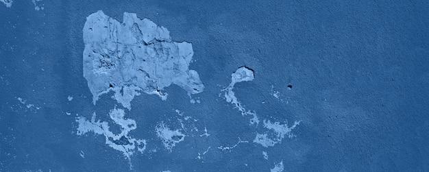 Старая треснутая монохромная стена. окрашенные текстуры фона в модном спокойном цвете. баннер. модный синий и спокойный цвет.