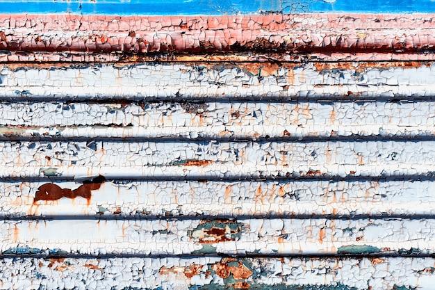 古いひびの入った錆びた塗料板張りの背景テクスチャのクローズアップ